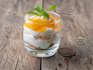 Healthy layered dessert with yogurt, banana, mango jam, cookie on wooden background, side view.