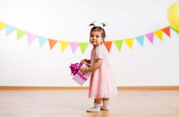 childhood, people and celebration concept - happy baby girl with gift box on birthday party