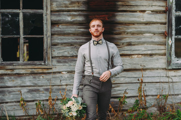 Hipster. Stylish groom with beard posing outdoors