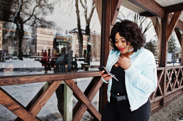 Stylish african american plus size model with mobile phone at hand against wooden cafe at winter day.