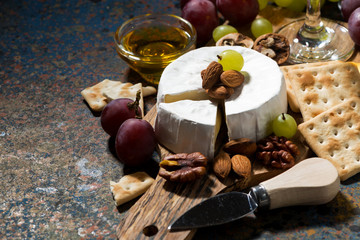 snacks and camembert cheese on a dark background