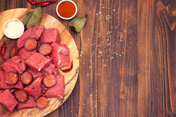 raw meat with smoked sausage on wooden board