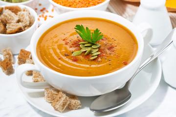 soup of pumpkin and lentils in a bowl, closeup