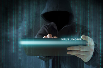 Unrecognizable hooded hacker using tablet for virus loading. Cyber crime, stealing data and identity theft concept.