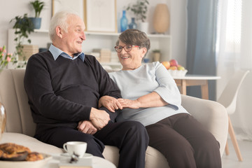 Grandparents sitting on couch