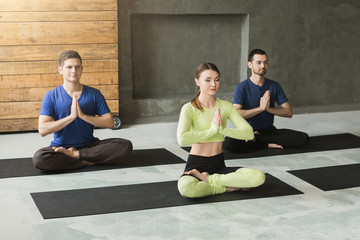 Young woman and men in yoga class, relax meditation pose