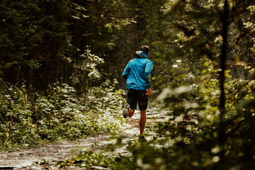Fototapete - athlete runner in blue sports jacket forest trail in rain