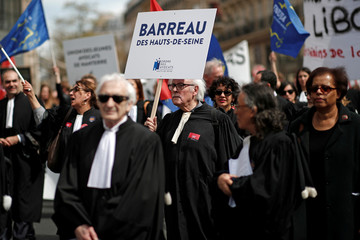 Magistrates, clerks and lawyers attend a demonstration as a part of a national profession-wide strike against planned justice reform law in Paris