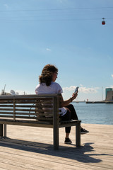 Portrait of a young woman sitting on a bench and looking at her smartphone in the port of Barcelona with the red cabin of a cableway in the background.