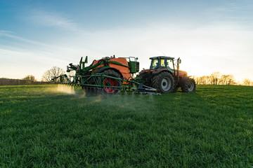 Ackerbau, Landwirt spritzt sei  Getreide am Abend gegen Unkräuter, Gegenlicht