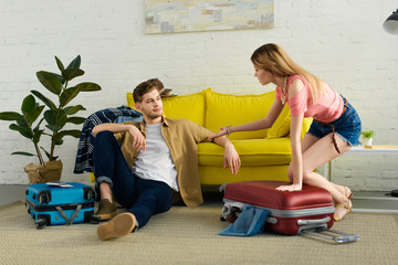 young couple packing suitcases and preparing for a vacation