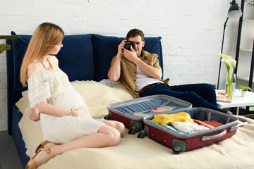 husband taking photo of pregnant wife preparing for vacation