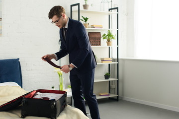 handsome businessman in suit packing travel bag in bedroom