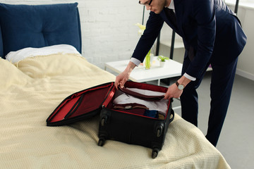 handsome professional businessman in suit packing baggage for business trip