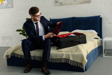 handsome businessman in suit packing bag for business trip