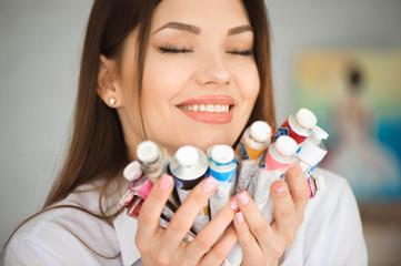 Young inspired girl choosing paint tube in light studio