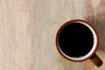 Black coffee on wooden table background. Top view. Free space for text.