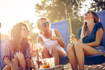 Group of young casual female friends sitting on beach on sun beds,hangout and relaxing.Joying in sunset.
