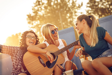 Group of young female friends sitting on beach on sunbeds,singing and playing guitar.Joying in sunset.