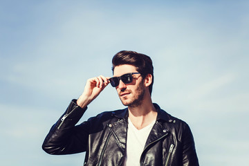 Confident handsome man in sunglasses and leather jacket over blue sky.