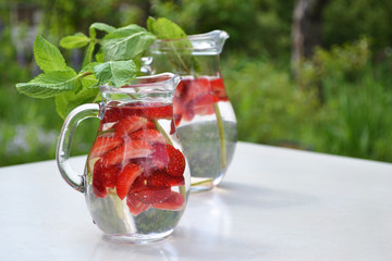 Strawberry  mint flavored water in glass jugs on summer outdoor background. Cold refreshing  .drinks in garden party. Detox water. Text space image