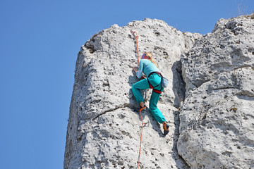 Poster de jardin Alpinisme A woman climbing the rocks.