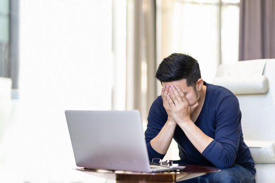 Stressed out asian man freelancer holding hand on his face. Young asian student feel tried, failure, stess, strain, exhausted and thinking his work.