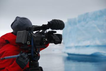 Cameraman filming an iceberg in Antarctica
