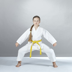 On a gray background the girl stands in a karate rack