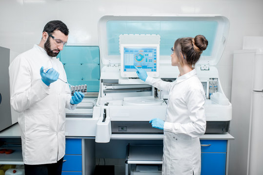 Laboratory assistants in unifrom working with professional medical analizer at the laboratory