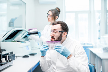 Funny portrait of a male laboratory assistant with test tubes and analyzer machines sitting at the modern laboratory