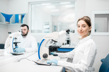 Fototapeta Portrait of two medics in uniform working with microscope making analysis at the laboratory office