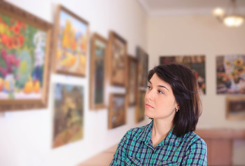 Young woman looking at painting.