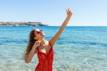 Girl in swimsuit with a smart phone on the beach. Girl taking fun selfie at the beach