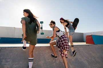 Happy female friends running over skateboard ramp