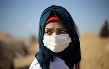 Palestinian medic wears mask to protect herself from tear gas fired by Israeli troops in southern Gaza Strip