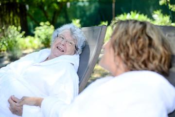 cheerful mature woman with her mother elderly senior female with bathrobe in spa resort garden