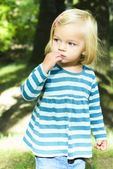Portrait of curious little Caucasian girl wearing dress looking in park