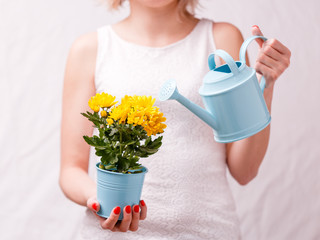 Photo of woman holding pot with yellow flower and watering can