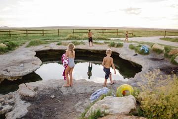 Children standing near pool next to field
