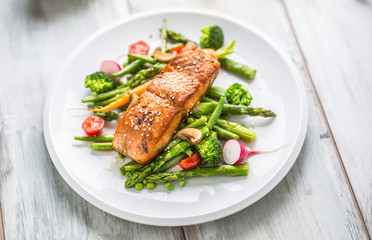 Foto op Textielframe Vis Roasted salmon steak with asparagos broccoli carrot tomatoes radish green beans and peas. Fish meal with fresh vegetable