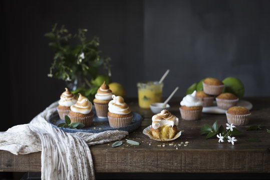 Cupcakes with meringue on wooden table