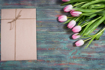 Pink tulips flowers with gifts boxes on wooden background. Selective focus, place for text