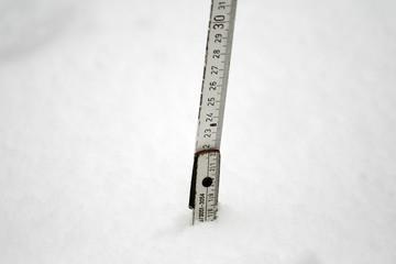Schneehöhe mit Zollstock messen nach Schneefall im Winter