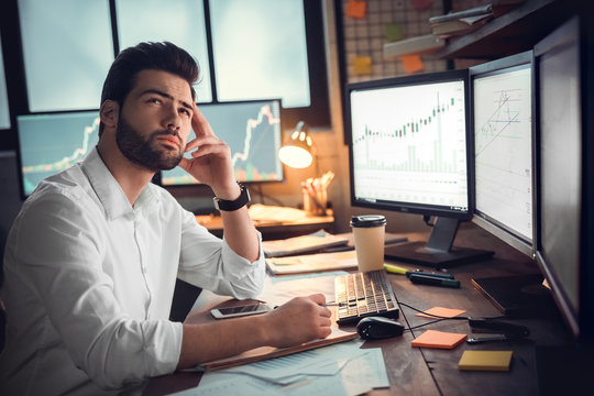 Businessman thinking and using computer of trading graph