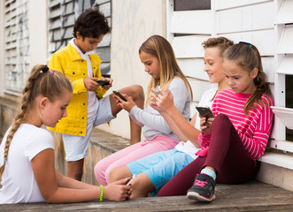 Cheerful children are chatting on their smartphone