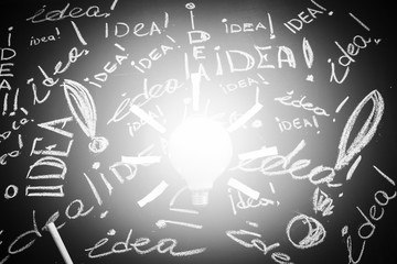 Light bulb with rays made from yellow stickers on the black chalkboard with titles idea.