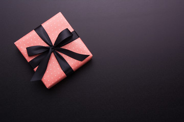 Hands holding wrapped gift box with colored ribbon as a present for Christmas, new year, mother's day, anniversary, birthday, party, on black background, top view. Present for a colleague at work.