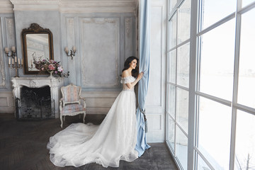 Beautiful bride, young model brunette woman, in stylish wedding dress with naked shoulders, with bouquet of flowers in her hands, posing in luxury vintage interior
