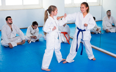 Pair of girls are trying in sparring to use new moves